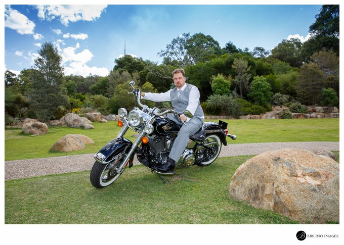 Groom poses on a harley davidson on the rock garden lawn at the National Botanical Gardens
