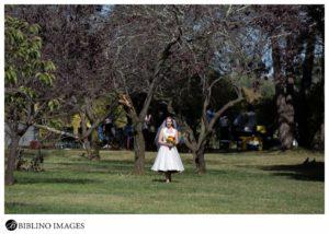 Bride wlalks along the grass at Lennox park