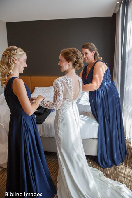Bridesmaids help bride in to her wedding dress